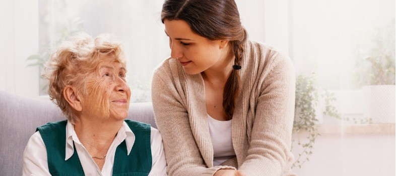 Older woman sitting with a healthcare worker, looking at each other and smiling